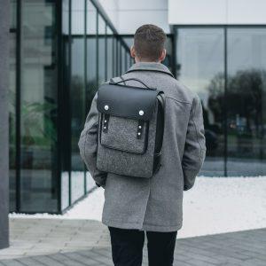szürke filc hátizsák fekete bőr részletekkel, szürke szövetkabáttal viselve
