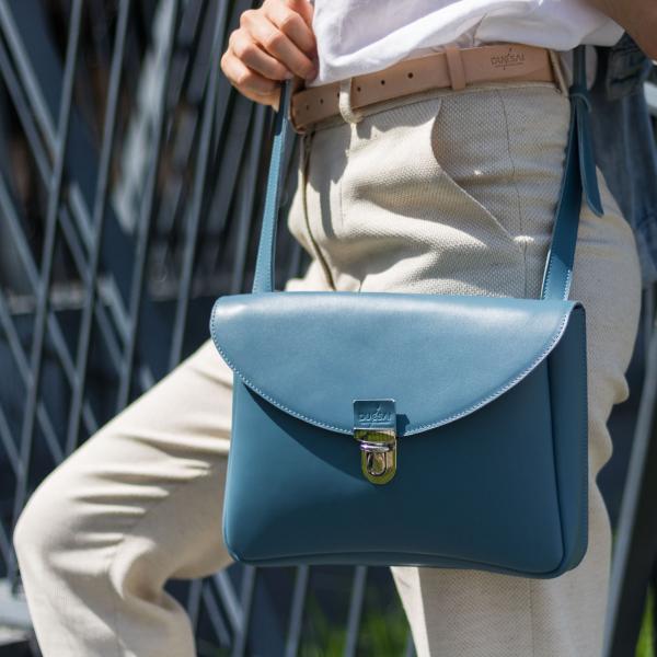 kék eve táska natúr vászon nadrággal és fehér blúzzal viselve