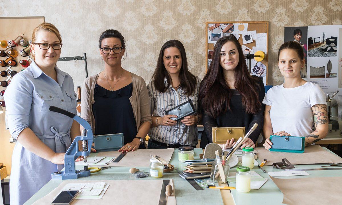 workshop résztvevők boldogan pózolnak az általuk készített tárcákkal